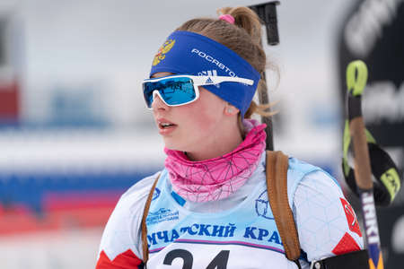 Portrait sportswoman biathlete Vlada Shishkina St. Petersburg at finish after skiing, rifle shooting. Open regional junior biathlon competitions East Cup. Kamchatka Peninsula, Russia - April 12, 2019 에디토리얼