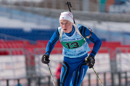 Kamchatka sportsman biathlete Protasov Dmitry skiing on ski track distance biathlon stadium. Junior biathlon competitions East of Cup. Petropavlovsk City, Kamchatka, Russian Far East - April 14, 2019.