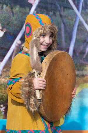 Girl dancing with tambourine in national clothing indigenous inhabitants Kamchatka. Concert, celebration Koryak national ritual holiday Day of Seal - Hololo. Kamchatka Region, Russia - Nov 4, 2018