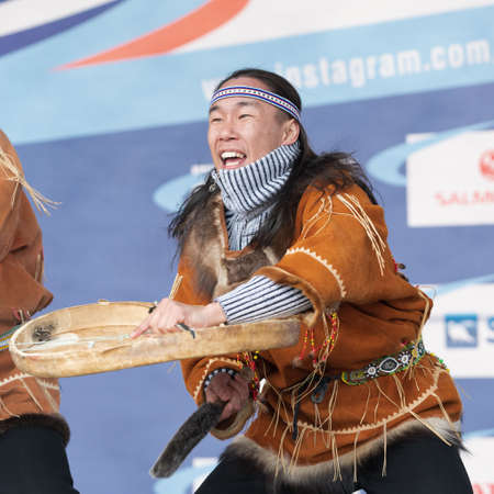 Aboriginal dancer in national clothes of native people emotional dancing with tambourine. Concert Koryak Dance Ensemble Mengo during Russian Alpine Skiing Championship. Kamchatka, Russia - Apr 2, 2019