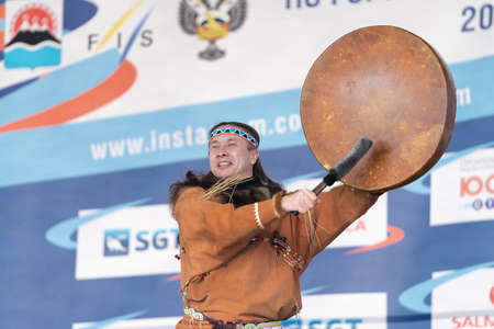 Male dancer in national clothes aboriginal people expression dancing with tambourine. Concert Koryak Dance Ensemble Mengo during Russian Alpine Skiing Championship. Kamchatka, Russia - April 2, 2019.