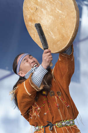 Aboriginal dancer in traditional clothes of native people dancing with tambourine. Concert Koryak Dance Ensemble Mengo during Russian Alpine Skiing Championship. Kamchatka, Russia - April 2, 2019 에디토리얼