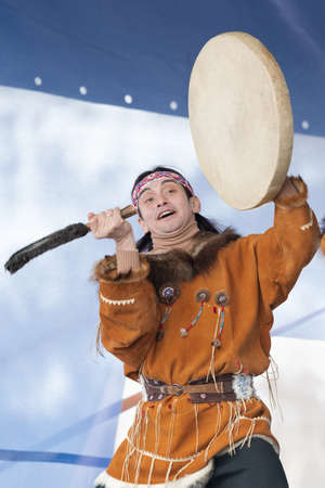 Aborigine dancer in traditional clothes native people expression dancing with tambourine. Concert Koryak Dance Ensemble Mengo during Russian Alpine Skiing Championship. Kamchatka, Russia - Apr 2, 2019