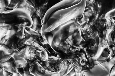 Abstract plume of natural black smoke and white huge flame of strong fire, motion blur from fire, high temperature flames. Dramatic moody black and white image. Dangerous firestorm abstract background