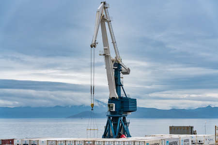 Harbor gantry-crane and many containers for shipping sea storage at terminal in sea port on coast of Pacific Ocean. Petropavlovsk-Kamchatsky City, Kamchatka Peninsula, Russian Far East - Aug 27, 2019. 에디토리얼