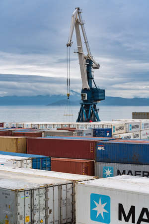 Harbor gantry crane and many containers for shipping sea storage at terminal in sea port on coast of Pacific Ocean. Petropavlovsk-Kamchatsky City, Kamchatka Peninsula, Russian Far East - Aug 27, 2019.