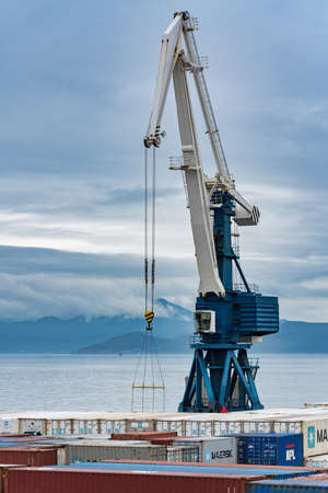 Harbor portal crane and many containers for shipping sea storage at terminal in sea port on coast of Pacific Ocean. Petropavlovsk-Kamchatsky City, Kamchatka Peninsula, Russian Far East - Aug 27, 2019.