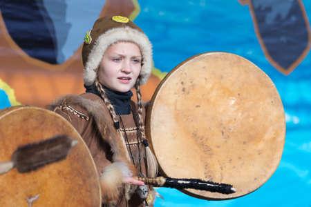 Girl dancing with tambourine in national clothing indigenous inhabitants Kamchatka. Concert, celebration Koryak national ritual holiday Hololo - Day of Seal. Kamchatka Region, Russia - Nov 4, 2018 Editöryel