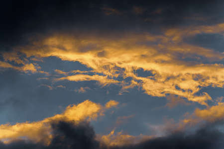 Stunning fluffy thunderstorm clouds illuminated by disappearing rays at sunset and dark thunderclouds floating across sunny blue sky to change season weather. Natural meteorology abstract background. 스톡 콘텐츠