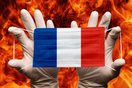 Doctor holding in white gloves protection medical face mask, respiratory bandage with France national country flag superimposed on mask. Concept on background of dangerous red flames natural fire