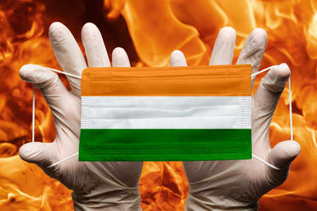 Doctor holding in white gloves protection medical face mask, respiratory bandage with India national country flag superimposed on mask. Concept on background of dangerous red flames natural fire