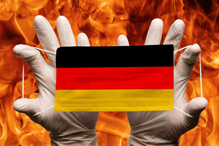 Doctor holding in white gloves protection medical face mask, respiratory bandage with Germany national country flag superimposed on mask. Concept on background of dangerous red flames natural fire