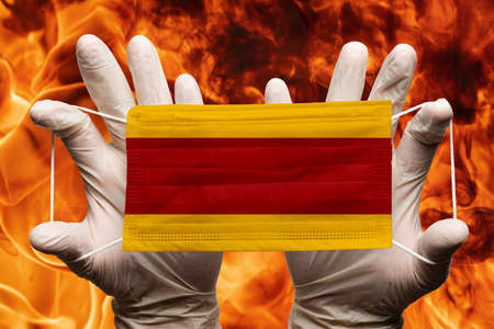 Doctor holding in white gloves protection medical face mask, respiratory bandage with Spain national country flag superimposed on mask. Concept on background of dangerous red flames natural fire