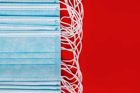 Surgical and medical face masks for coronaviruse on red background. Close-up view of lot respiratory face bandage with rubber ear straps. Copy space, concept protection, 2019-ncov, virus prevention.