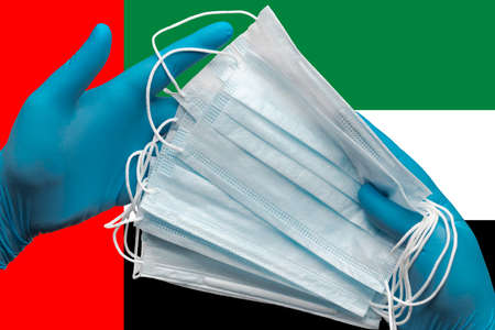 Medic holding respiratory face mask in hands in blue gloves on background national flag of United Arab Emirates UAE. Concept pandemic insurance coronavirus, flu, quarantine, pandemic outbreak, grippe.