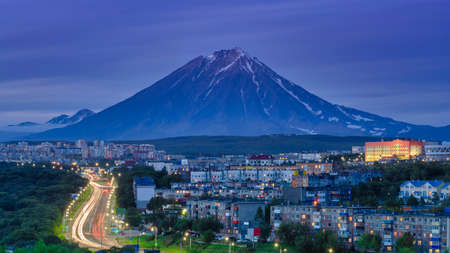Panorama of night city of Petropavlovsk-Kamchatsky on background cone of volcano, urban development at twilight, backlit city road with driving car lights.