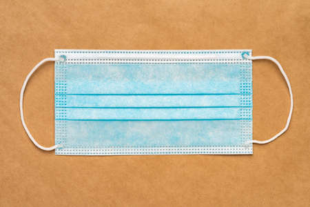 Blue medical surgical face mask with rubber ear straps on yellow craft paper background. Flat lay, close-up view. 免版税图像