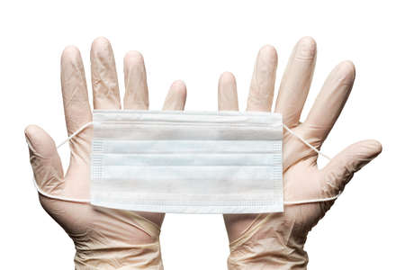 Human hands holding surgery medical face mask in white gloves isolated on white background. Medicinal concept hygiene and health care, protective clothing during global pandemic, coronavirus.