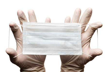 Doctor holding surgery medical face mask in hands in gloves isolated on white background. Medicinal concept protective clothing, equipment during corona virus, global pandemic, hygiene and health care Фото со стока