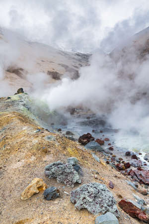 Mountain landscape, crater of active volcano: fumarole, hot spring, lava field, gas-steam activity. Dramatic volcanic landscape, popular travel destinations for active vacation, mount climbing, hiking Фото со стока