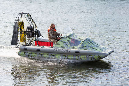 Man in camouflage uniforms and life jacket riding airboat along water surface. Inflatable rubber air boat sail on river at speed. Kamchatka Peninsula, Russian Far East - August 20, 2015