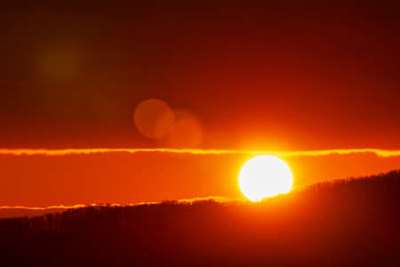 Beautiful sunrise in mountains, red orange sun disk rises from tops of mountain range. Natural lens flare in sky, sunbeam light leaks.