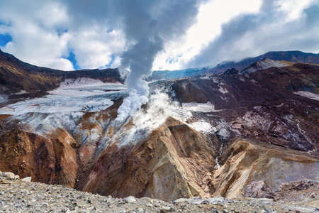 Dramatic volcanic landscape, caldera of active volcano: hot spring, fumarole, lava field, geothermal gas-steam activity in crater. Mountain landscape, travel destinations for active vacation, hiking