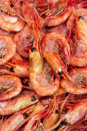 Group of boiled frozen wild shrimp with caviar cooked in sea water. Background of lot small aquatic crustaceans. Prawn - East Asia delicacy cuisine as an appetizer. Close-up flat lay view of seafood. Фото со стока