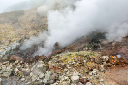 Breathtaking view of volcanic landscape, aggressive hot spring, eruption fumarole, gas-steam activity in crater of active volcano. Dramatic mountain landscape, travel destinations for active vacation. Фото со стока
