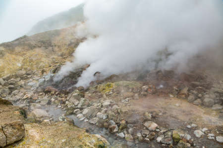 Picturesque view of volcanic landscape, aggressive hot spring, erupting fumarole, gas-steam activity in crater active volcano. Scenery mount landscape, travel destinations for hike, active vacation.