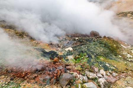 Mysterious view of volcanic landscape, aggressive hot spring, eruption fumarole, gas-steam activity in crater of active volcano. Picturesque mount landscape, travel destinations for vacation, hiking.
