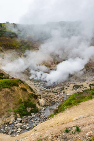 Exciting view of volcanic landscape, eruption fumarole, aggressive hot spring, gas-steam activity in crater of active volcano. Beautiful mountain landscape, travel destinations for active vacation.