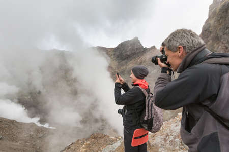 Tourists takes pictures of dramatic volcanic landscape, aggressive hot springs, eruption fumarole, gas-steam activity in crater active volcano. Kamchatka Peninsula, Russian Far East - Sep 8, 2014. Фото со стока