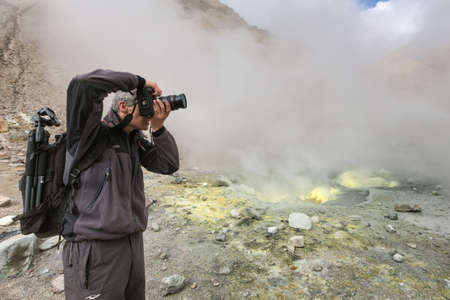 Male photographer takes pictures volcanic landscape, fumes aggressive hot springs, eruption fumarole, gas-steam activity in crater active volcano. Kamchatka Peninsula, Russian Federation - Sep 8, 2014 Фото со стока