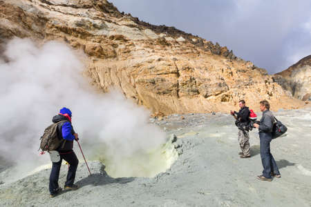 Group tourists watching eruption of hot springs, fumes fumarole, volcanic gas-steam activity in crater active volcano, beautiful mountain landscape. Kamchatka Peninsula, Russian Far East - Sep 8, 2014
