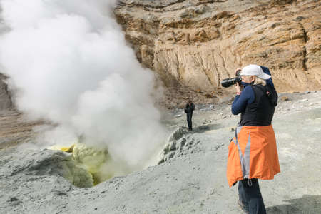 Woman photographer tourist takes pictures of volcanic landscape, hot springs, eruption fumarole, gas-steam activity in crater active volcano. Kamchatka Peninsula, Russian Far East - September 8, 2014. Фото со стока