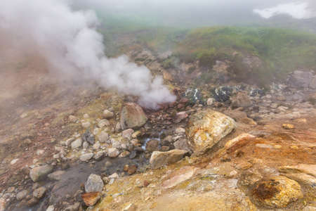 Breathtaking view of volcanic landscape, erupting fumarole, aggressive hot spring, gas-steam activity in crater of active volcano. Beautiful mountain landscape, travel destinations for active vacation