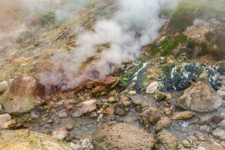 Thrilling view of volcanic landscape, aggressive hot spring, eruption fumarole, gas-steam activity in crater of active volcano. Scenery mountain, travel destinations for active vacation and hiking. Фото со стока