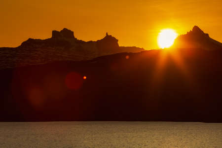 Beautiful sunset in rocky mountains and lake shore, red orange sun sets behind silhouette of cliff mountain range, picturesque landscape. Natural lens flare in yellow sky, sunlight leaks.