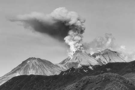 Mountain landscape of Kamchatka, dramatic view of eruption of active Zhupanovsky Volcano, plume of gas, steam and ashes from crater. Black and white photo, filter noise and grain, effect of old film.