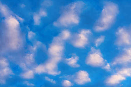 Beautiful clouds in blue sky, illuminated by rays of sun at sunset to change summer weather. Soft focus, motion blur multicolored abstract background.