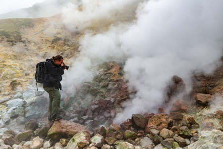 Male photographer takes pictures of aggressive volcanic landscape, hot spring, eruption fumarole, gas-steam activity in crater active volcano. Kamchatka Peninsula, Russian Far East - September 7, 2014 Фото со стока