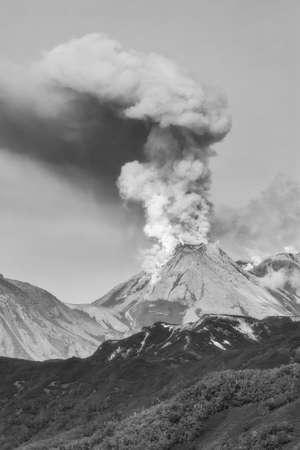 Dramatic volcanic landscape, beautiful view of erupting of Zhupanovsky Volcano, plume of steam, gas, ashes from crater active volcano. Black and white image, filter noise and grain, effect of old film