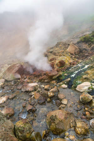 Exciting view of volcanic landscape, erupting fumarole, aggressive hot spring, gas-steam activity in crater of active volcano. Dramatic mount landscape, travel destinations for active vacation, hike.