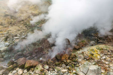 Exciting view of volcanic landscape, erupting fumarole, aggressive hot spring, gas-steam activity in crater of active volcano. Beautiful mountain landscape, travel destinations for active vacation.
