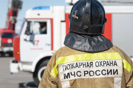 Back view of inscription Emercom of Russia on uniform firefighter of Ministry of Civil Defence, Emergencies and Disaster Relief of Russian Federation MChS. Kamchatka Peninsula, Russia - April 27, 2019 Фото со стока