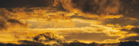 Panorama dramatic clouds illuminated rising of sun in sky to change weather. Natural meteorology background. Soft focus, motion blur sky majestic meteorology cloudscape.