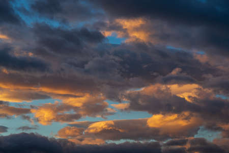 Stunning colorful thunderclouds in blue sky, illuminated by rays of sun at sunset to weather change.