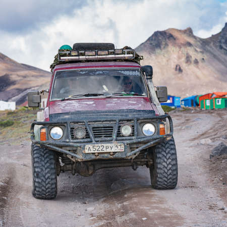 Old four-wheel drive vehicles Nissan Patrol driving on rocky mountain road on background volcanic landscape. Expedition in travel destinations to volcano. Kamchatka Peninsula, Russia - August 29, 2019