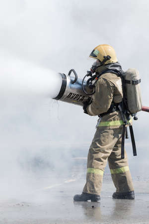 One firefighter extinguish fire from fire hose, using firefighting water-foam barrel with air-mechanical foam. Professional holiday Firefighters Day. Petropavlovsk-Kamchatsky, Russia - April 27, 2019